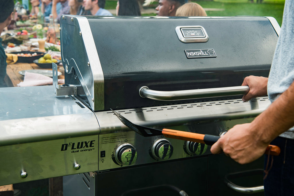 man with his hand on the handle of a Nexgrill lid