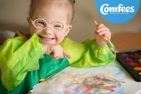 Smiling little girl painting