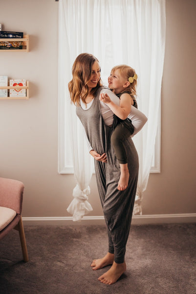 Matching mom and daughter rompers in gray.