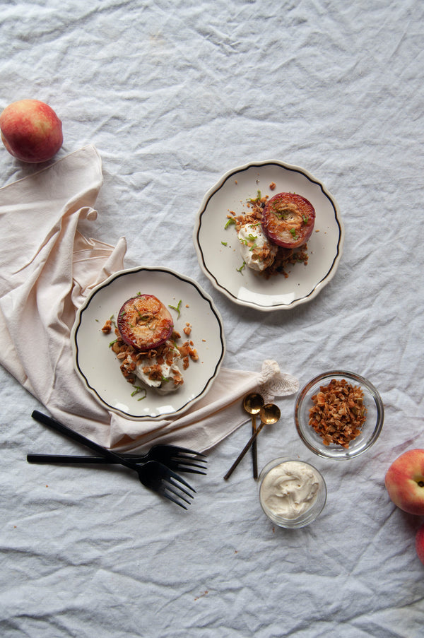 Grilled Brown Butter Peaches with Vanilla Bean Creme Fraiche from Vermont Creamery. Topped with fresh mint and rosemary granola for crunch. The perfect dessert for a simple BBQ.