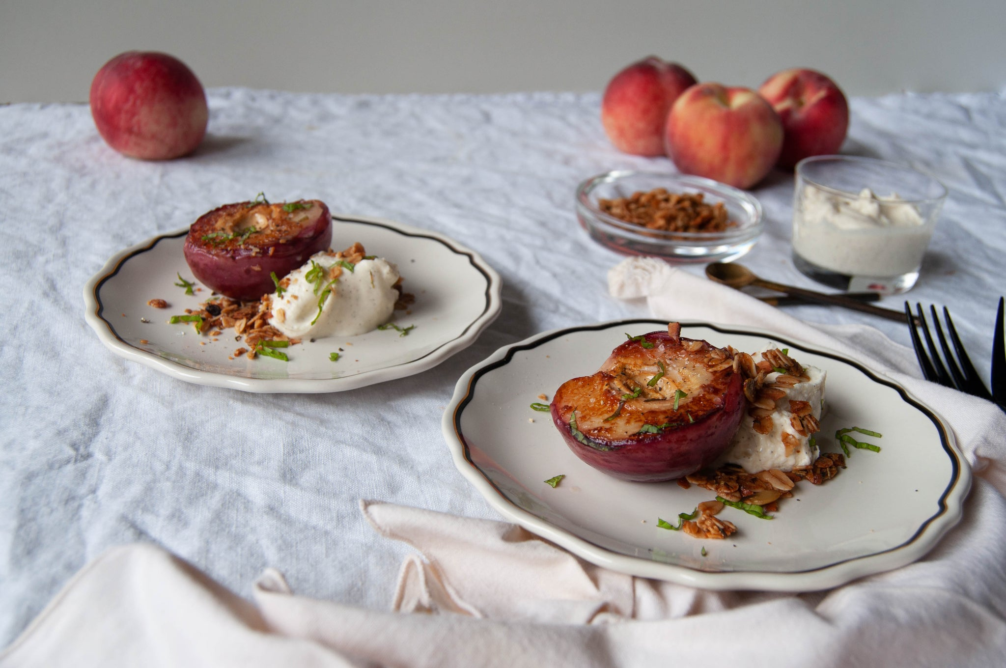 Delicious and simple grilled brown butter peaches. Served with vanilla bean creme fraiche, mint, and rosemary granola. Indulgent yet simple.
