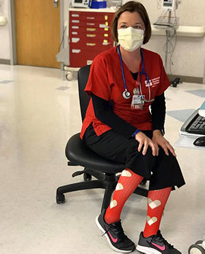 Nurse sitting in hospital wearing PRO Compression Bandage Hearts socks during her shift.