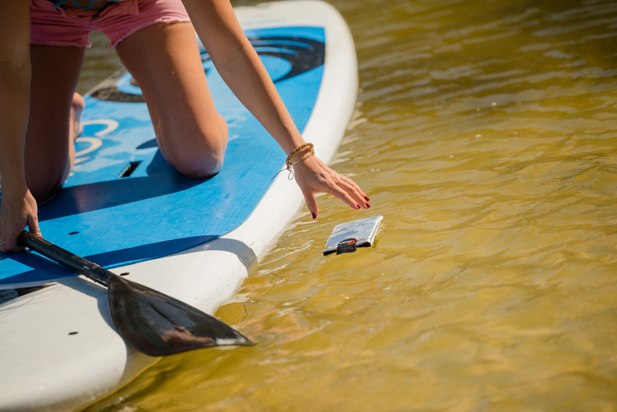 Girl on paddle board picking up PHOOZY XP3 Series that is floating in the water