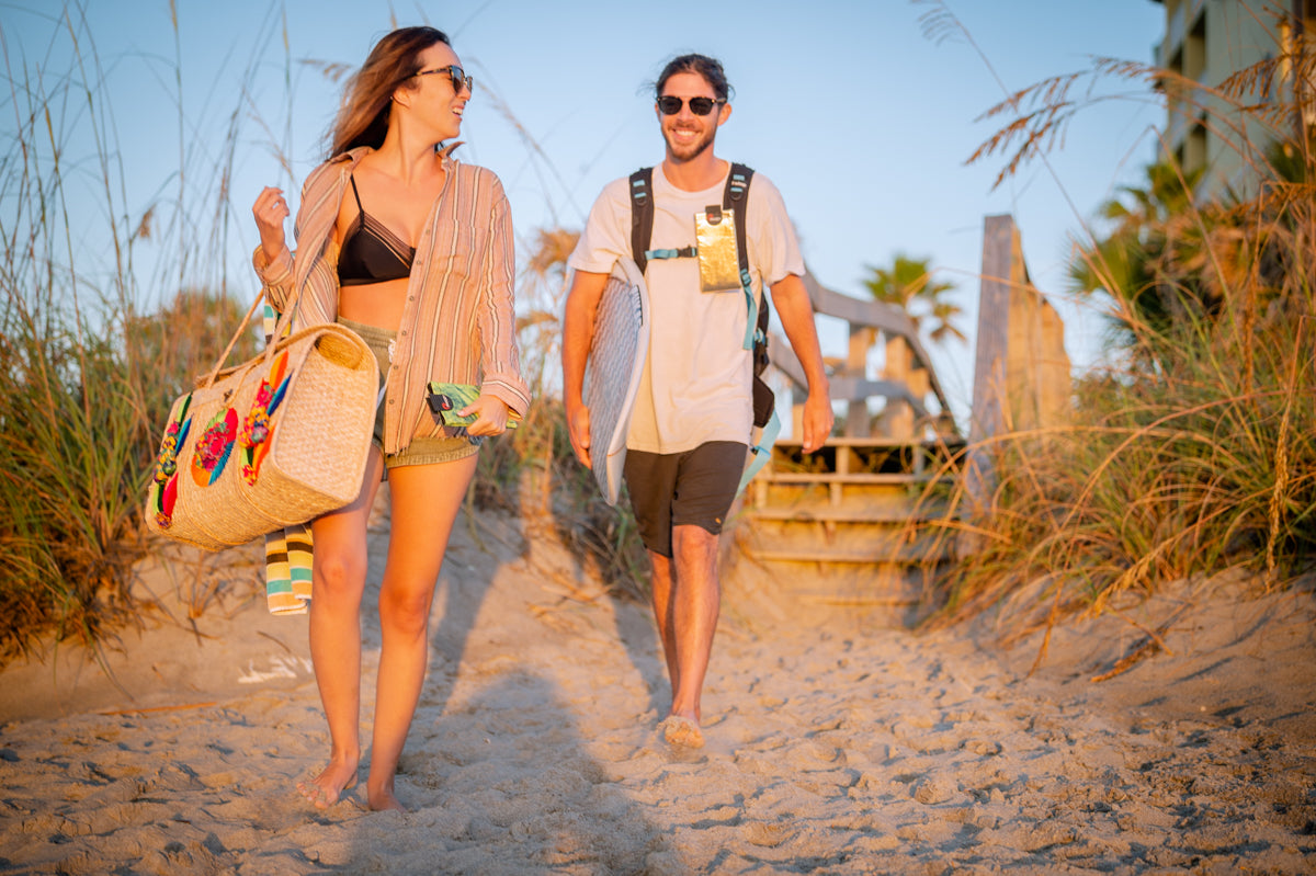 girl and guy walking on beach with beach bag, phoozy thermal capsules and surfboard
