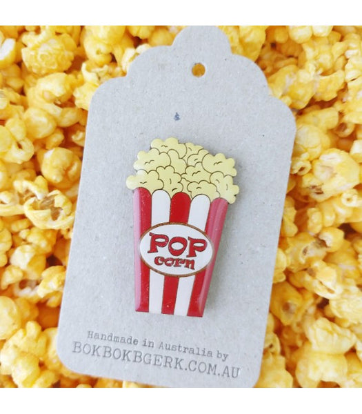 popcorn brooch on packaging with popcorn background
