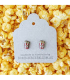 popcorn earrings on packaging with popcorn background.