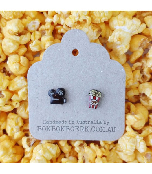 popcorn and movie camera earrings on packaging with popcorn background