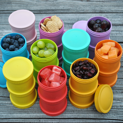 Re-Play Snack Stacks in different colours full of fruit and snacks. Lifestyle Image.