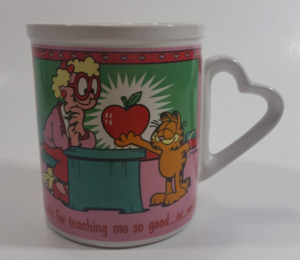 "Enesco United Features Syndicate Jim Davis ""Thanks for teaching me so good...er...well!"" Garfield Giving Apple To Teacher Ceramic Coffee Mug with Heart Shaped Handle"