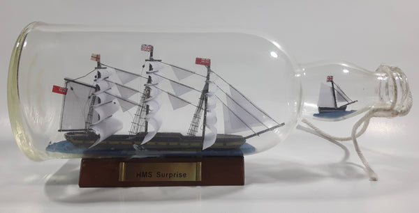 "Vintage Highly Detailed HMS Surprise British Flagged Captured French Naval Tall Ship with Small Skiff Life Boat Sail Boat in 10 1/4"" Long Glass Bottle"