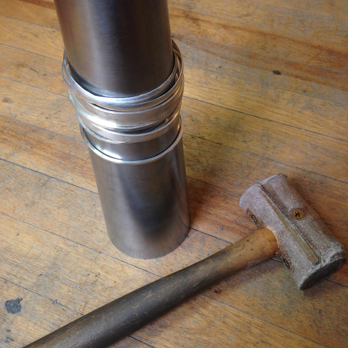 Hammer and bangles being formed on a bracelet mandrel.
