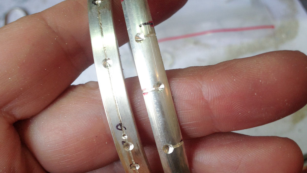 A hand holding two almost completed bangles.