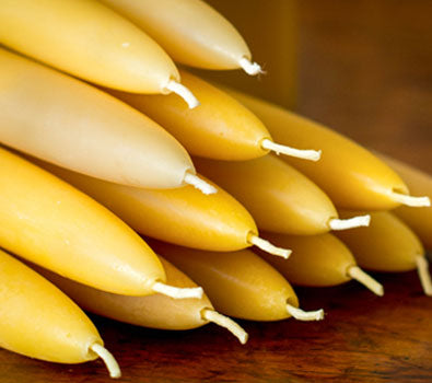 A stack of pale yellow beeswax candles