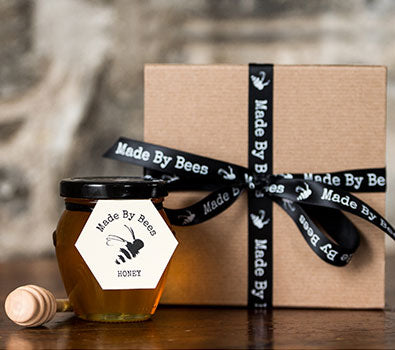 A jar of Made by Bees honey beside a gift box with a black bow