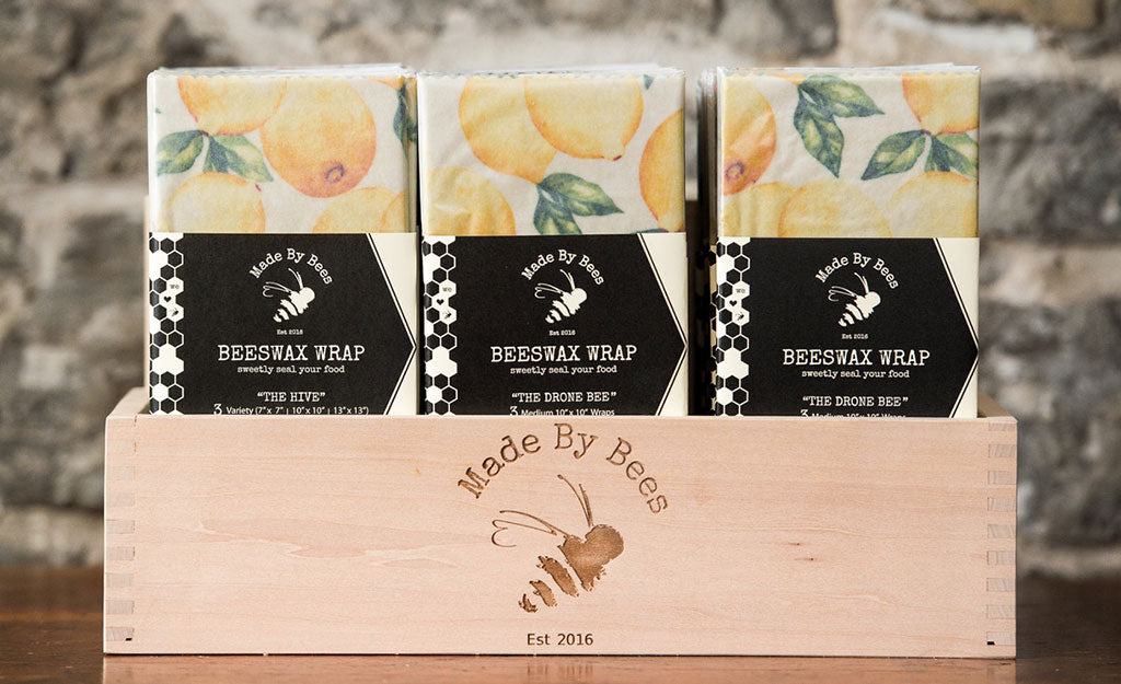 A wooden crate branded Made by Bees, filled with beeswax food wraps with a lemon pattern.