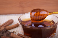 A bowl of amber coloured honey with a honey dipper on a table with cinnamon sticks