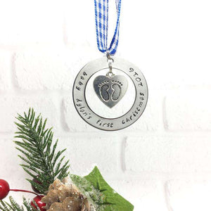 A baby's first Christmas decoration hanging on a blue ribbon