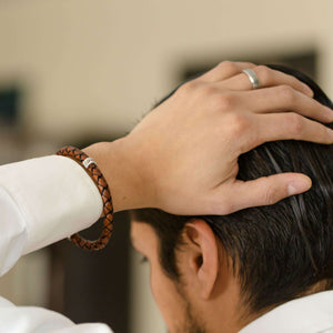 Man wearing personalised leather bracelet with his hand on his head