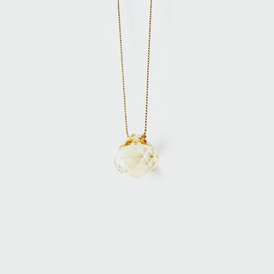 Champagne gold crystal teardrop on a beige silk cord necklace.  14k gf clasp.