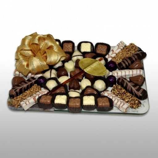 Rectangular Glass Tray Filled With Chocolates And Honey Straw
