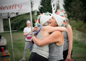Women wearing unicorn hats embracing