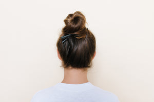 Black matte TopBun hair clip shown holding a high bun in brunette hair
