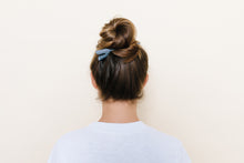 Gray matte TopBun hair clip shown holding a high bun in brunette hair