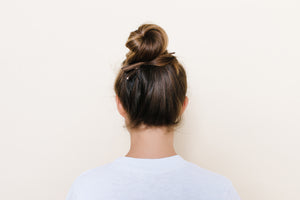 Medium brown TopBun hair clip shown holding a high bun in brunette hair