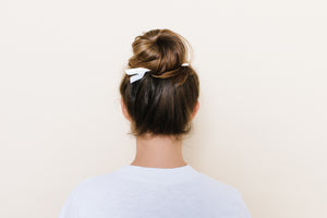 Glossy white TopBun hair clip shown holding a high bun in brunette hair