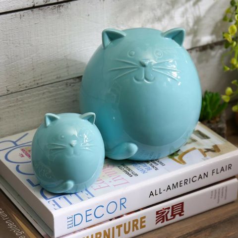 Cat figurine made from ceramic and featuring a soft blue finish.