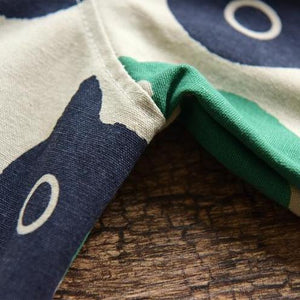Close up of the abstract cat print shirt in blue and green colors.