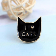 "Load image into Gallery viewer, This black cat pin features the print ""I Heart Cats"" in gold printed across a black cat face."