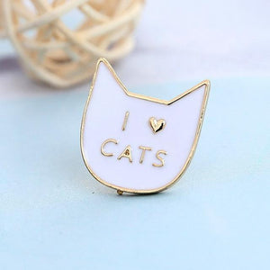 "This cat brooch features a white cat face and the text ""I Heart Cats"" printed in a golden hue."
