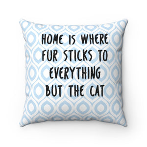 "This decorative cat pillow has the text ""Home is where fur sticks to everything but the cat"" printed in black on a white and blue argyle pattern."