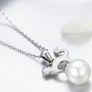 This sterling silver cat necklace pendant features a cute cat standing on an exquisite white pearl.