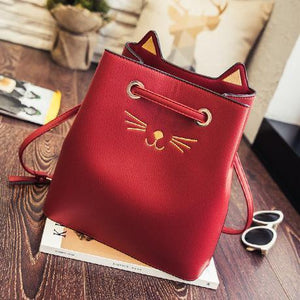 Red faux leather cat bag decorated with cat whiskers, nose, and ears.