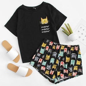 Womens cat pajamas featuring a black short-sleeve top and pajama pants with colorful cat faces printed on them