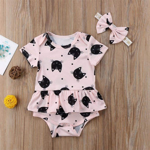 Baby cat onesie with a black cat print on a baby pink cotton fabric