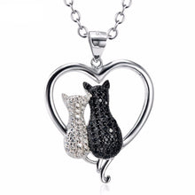 Load image into Gallery viewer, This White Cat Black Cat necklace features two cats encrusted with black and white crystals inside a sterling silver heart-shaped pendant.
