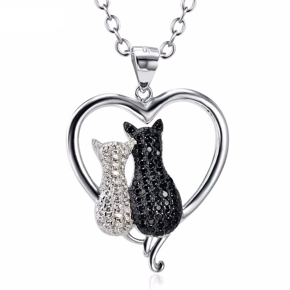 This White Cat Black Cat necklace features two cats encrusted with black and white crystals inside a sterling silver heart-shaped pendant.