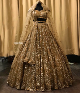 Gold bridal lehenga with heavy flared bottom and two dupattas