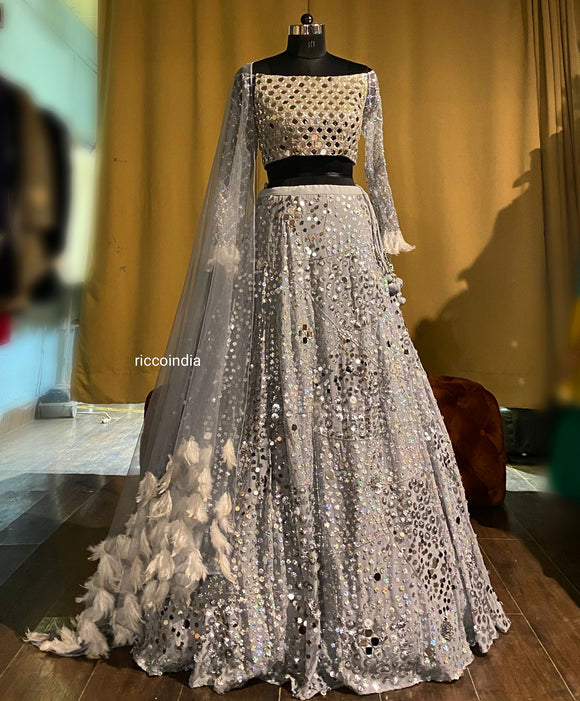 Silver lehenga with mirrorwork blouse and feather dupatta