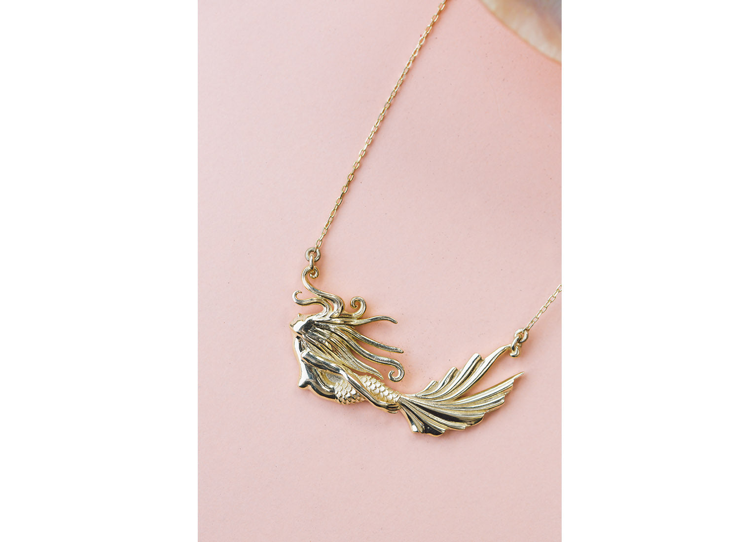A beautiful photograph of a mermaid pendent made from sterling silver and finished in gold. This unique piece of jewellery is designed by Lucky Culture
