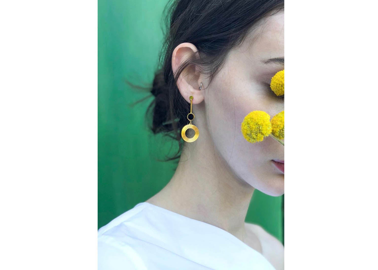 A model wearing beautiful contemporary earrings made from sterling silver and finished in 18k gold. these unique earrings are perfect for a valentines day gift