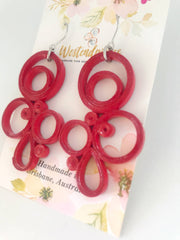 Red quilled earrings made from paper.