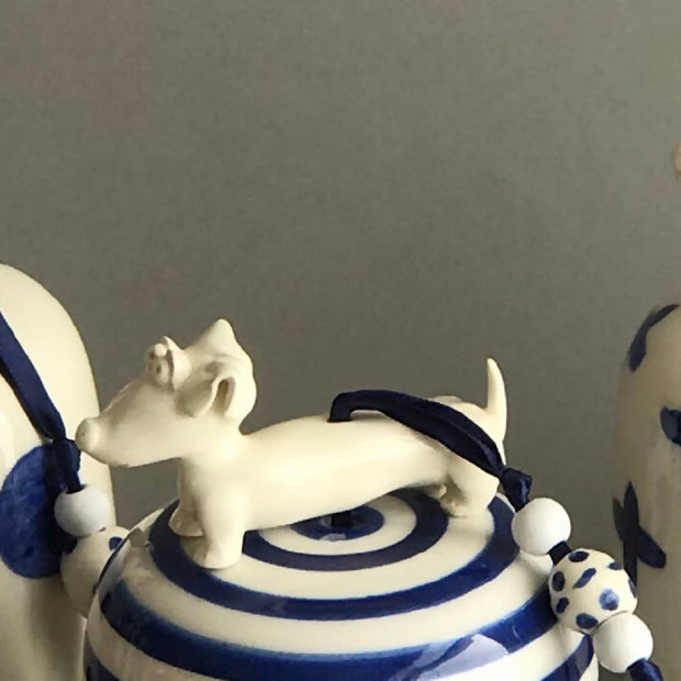 Blue and white ceramic bell with sausage dog
