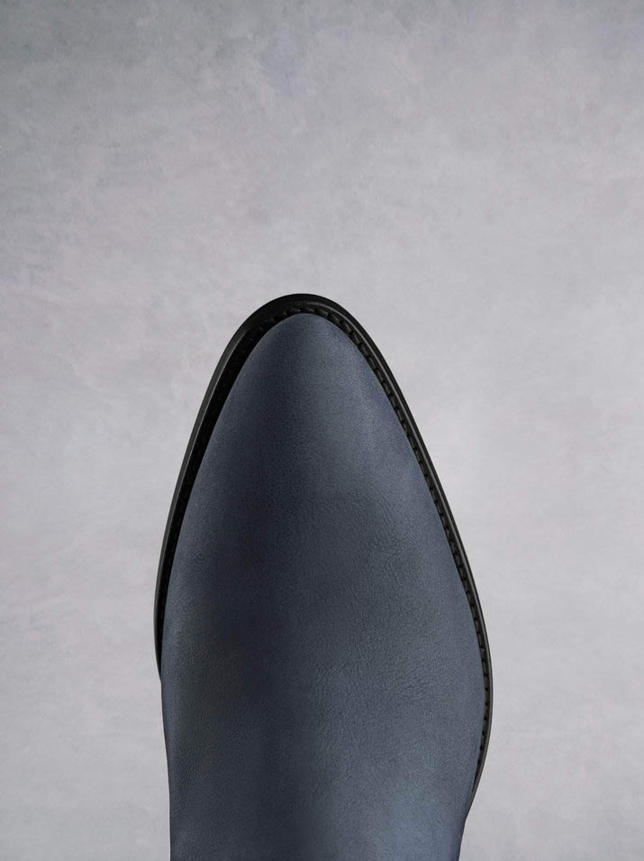 This petrol blue ankle boot features a western style pointed toe shape.