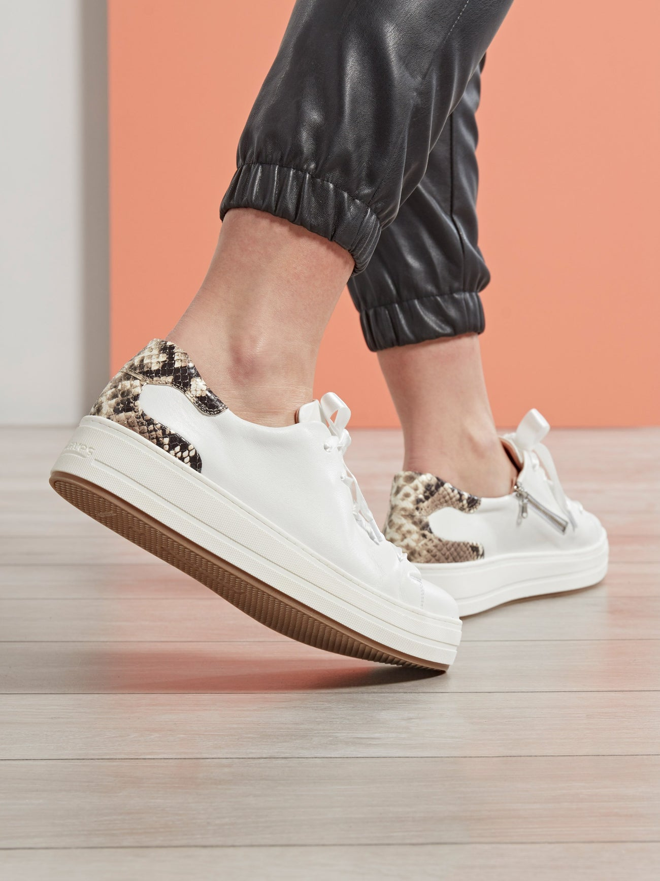 Churston, a trend-led flatform white trainer with a snake printed leather heel.