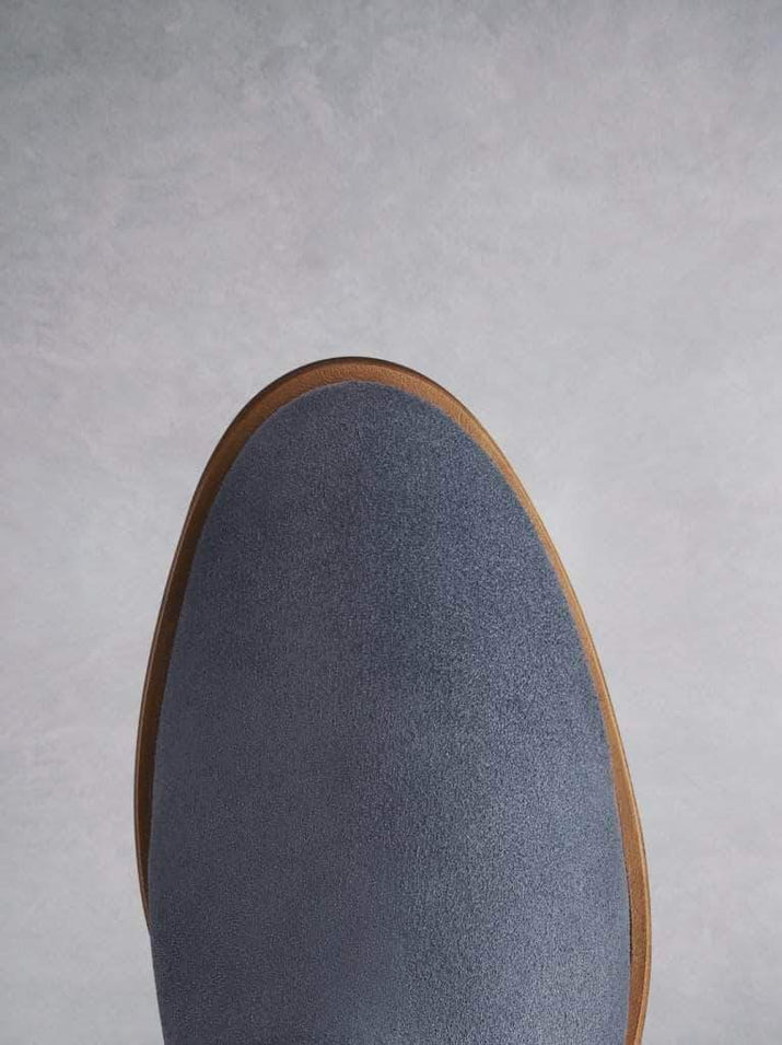 The blue suede boot has a smooth round toe shape.