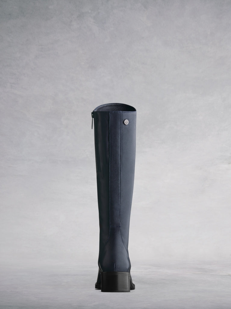 This navy boot has a smooth elegant back panel and a shorter knee high cut.